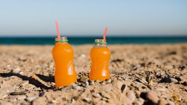 Uma garrafa de suco de plástico aberto com canudo vermelho na areia na praia