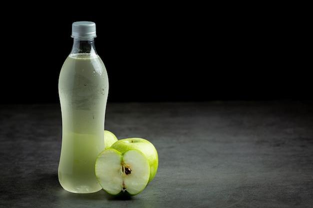 Uma garrafa de suco saudável de maçã verde colocada ao lado de maçãs verdes frescas