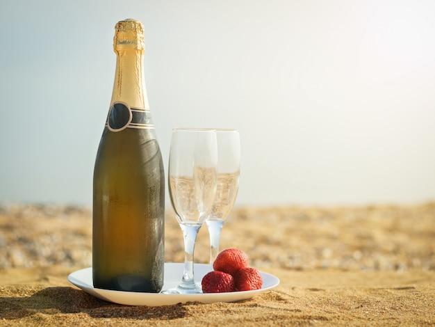 Uma garrafa de taças de champanhe frias e morangos em uma praia arenosa.