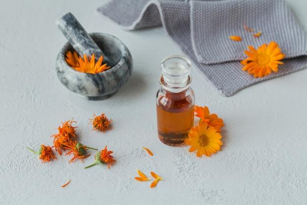 Uma garrafa de tintura de calêndula ou infusão com flores de calêndula frescas e secas em um fundo branco
