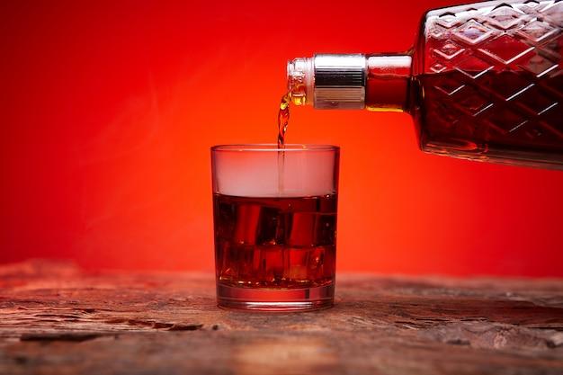 Uma garrafa de uísque e um copo de gelo