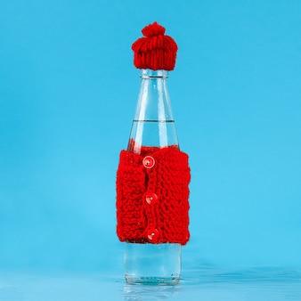 Uma garrafa de vidro com água fria está vestida com um chapéu e uma jaqueta quente. conceito de calor e geada.