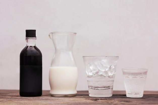 Uma garrafa de vidro com um líquido preto e uma jarra de vidro com leite