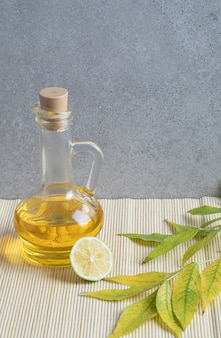 Uma garrafa de vidro de óleo com uma rodela de limão em um fundo cinza