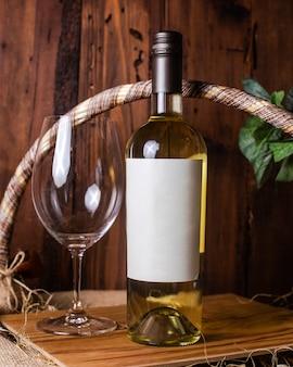 Uma garrafa de vinho branco vista frontal, juntamente com o copo vazio na mesa de madeira