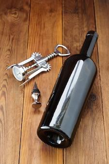 Uma garrafa de vinho com saca-rolhas, de madeira rústica. bebida de vinho plana leigos com copyspace.