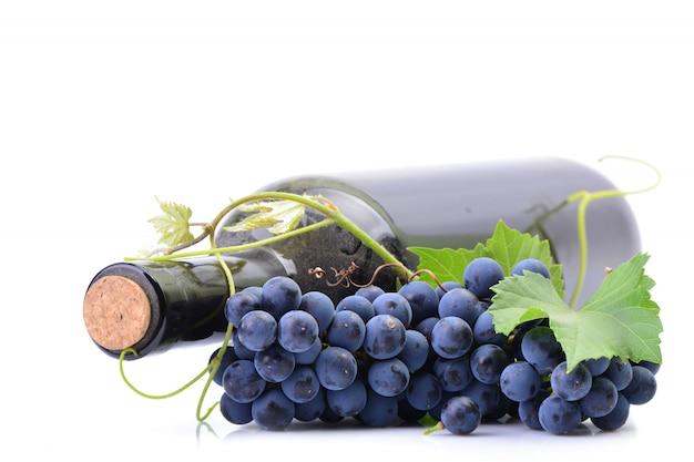 Uma garrafa de vinho com uvas isoladas