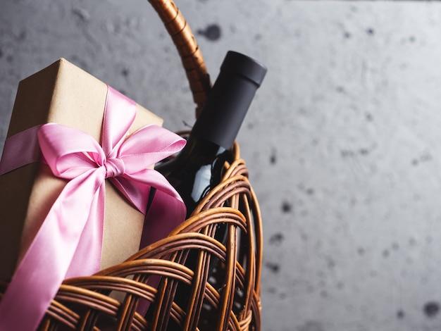 Uma garrafa de vinho tinto e uma caixa de presente com um laço em uma cesta com copyspace