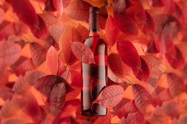 Uma garrafa de vinho tinto ou rosa em um fundo de folhas de outono, foto de close-up horizontal.