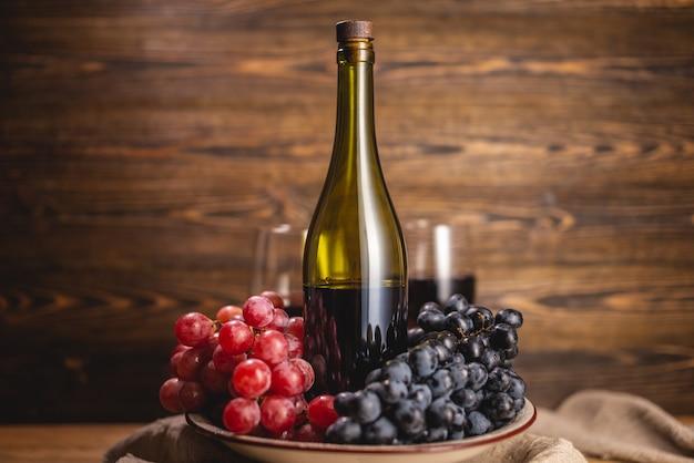 Uma garrafa de vinho tinto seco com um copo e um cacho de uvas em uma mesa de madeira