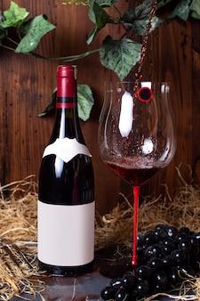 Uma garrafa de vinho tinto vista frontal de vinho tinto, juntamente com uvas pretas e folhas verdes, isoladas na bebida cinza adega de álcool de mesa