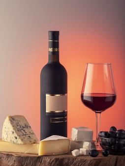 Uma garrafa de vinho, um copo de vinho tinto, queijo e uvas em uma mesa de madeira.