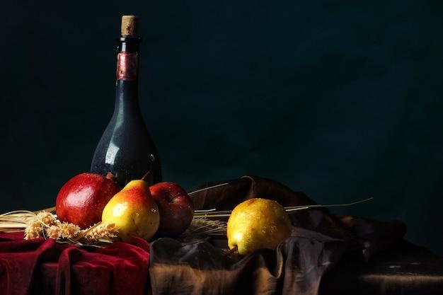 Uma garrafa de vinho velho e frutas maduras em um escuro