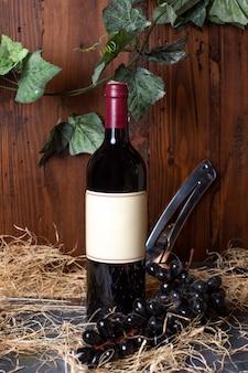 Uma garrafa de vista frontal da garrafa de álcool preto com tampa de borgonha, juntamente com uvas pretas e folhas verdes no fundo marrom bebe álcool da vinícola