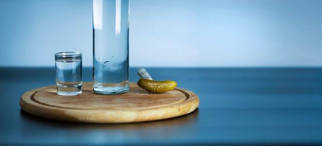 Uma garrafa de vodka, um copo e um pepino em conserva