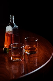 Uma garrafa e copos de licor na mesa de madeira