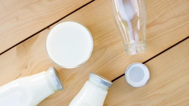 Uma garrafa e um copo de leite em uma mesa de madeira.