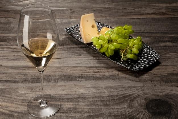 Uma garrafa e um copo de vinho branco com frutas sobre fundo de madeira