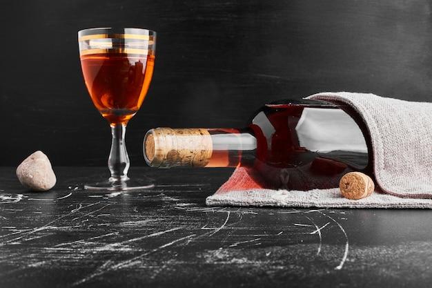 Uma garrafa e um copo de vinho rosé.