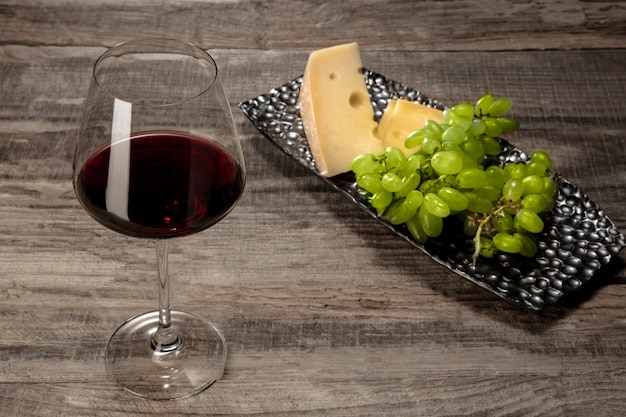 Uma garrafa e um copo de vinho tinto com frutas em mesa de madeira