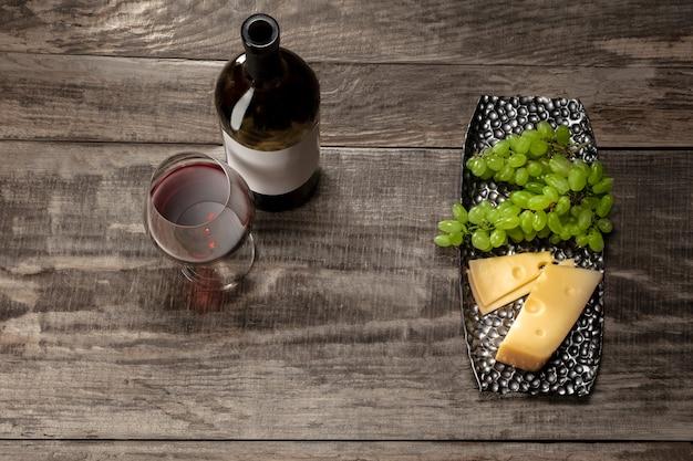 Uma garrafa e um copo de vinho tinto com frutas sobre fundo de madeira