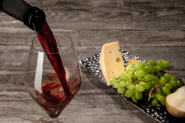 Uma garrafa e um copo de vinho tinto com frutas sobre madeira