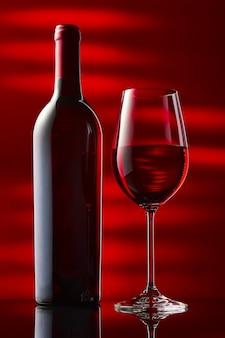 Uma garrafa e um copo de vinho tinto estão sobre uma mesa de espelho preta.
