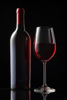 Uma garrafa e uma taça de vinho tinto estão sobre uma mesa de espelho preta.