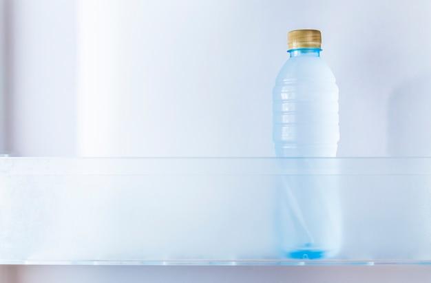 Uma garrafa fria de água potável na geladeira