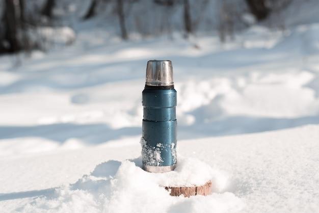 Uma garrafa térmica de metal azul em um toco de árvore com neve em uma floresta de inverno em um dia ensolarado