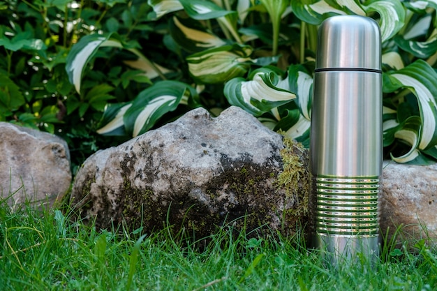 Uma garrafa térmica de metal para bebidas fica na grama, entre as pedras cobertas de musgo e folhas grandes ao fundo.
