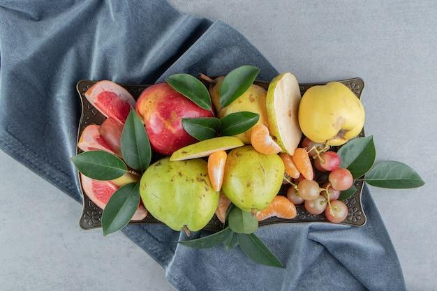 Uma generosa porção de frutas sortidas em uma bandeja de mármore