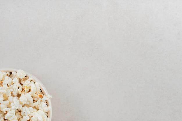 Uma generosa porção de pipoca em uma tigela branca na mesa de mármore.