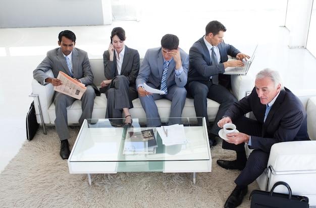Uma gente de negócios diversificada sentada em uma sala de espera