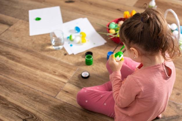 Uma ghirl bebê pintando ovos de páscoa em casa.