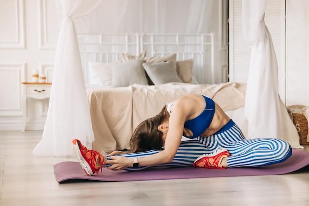 Uma ginasta de esportes com roupas esportivas azuis está se aquecendo e fazendo exercícios de alongamento