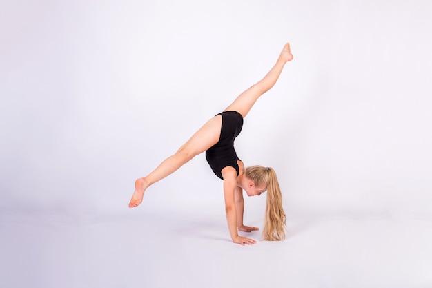 Uma ginasta faz fendas com as mãos em uma parede branca e isolada