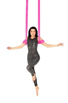 Uma ginasta faz um exercício em um pano rosa no ar em uma superfície branca