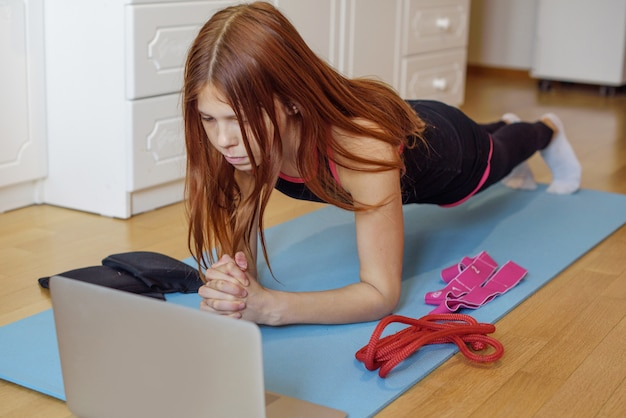 Uma ginasta garota treina em casa via conexão de vídeo em um laptop
