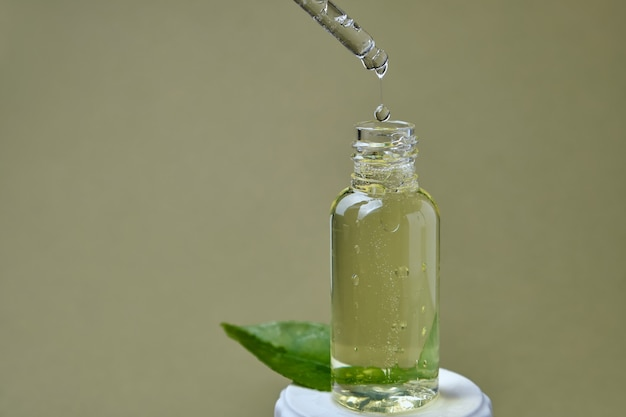 Uma gota de óleo cítrico e uma garrafa com uma folha no fundo verde oliva