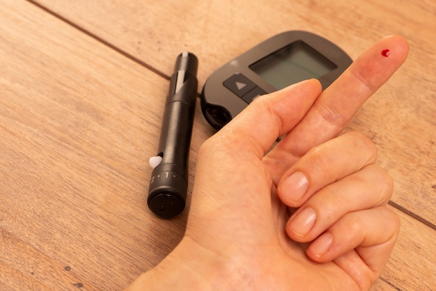 Uma gota de sangue no dedo de uma mulher para medir a glicose usando um glicosímetro.