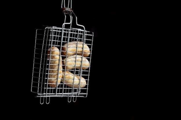 Uma grade de mão pequena é preenchida com salsichas grossas fritas sobre um fundo escuro