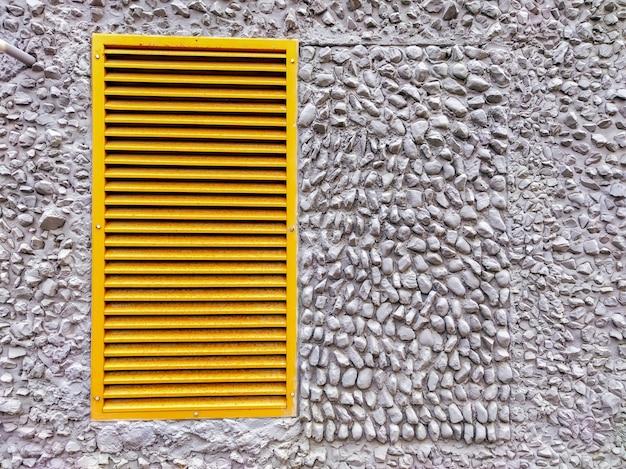 Uma grade de ventilação amarela em uma parede cinza