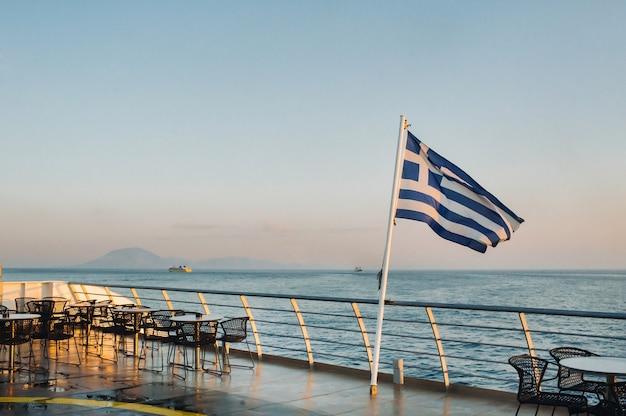 Uma grande balsa ao amanhecer no mar mediterrâneo com uma bandeira grega a bordo.