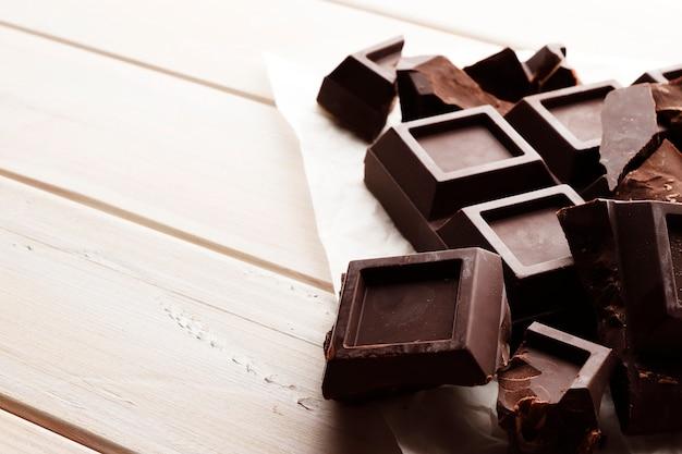 Uma grande barra de chocolate preto sobre um fundo branco de madeira com espaço para texto.