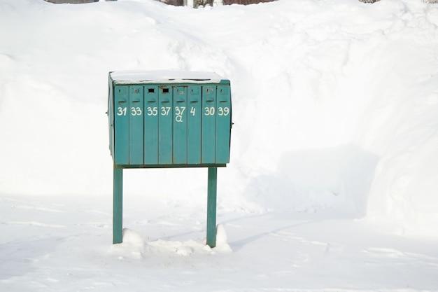 Uma grande caixa de correio verde com gavetas e números escritos nelas. inverno na rua.