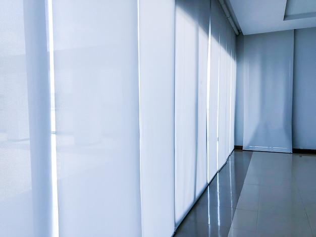 Uma grande cortina branca no escritório bloqueando a luz do sol no prédio pela manhã