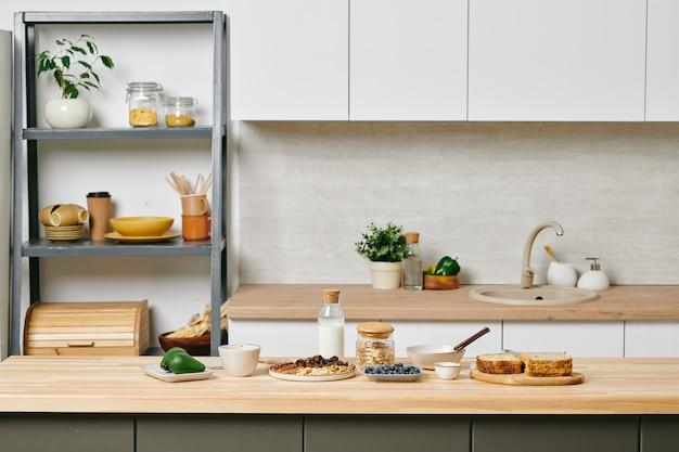 Uma grande cozinha moderna com uma prateleira cheia de utensílios de cozinha e mesa de madeira com comida