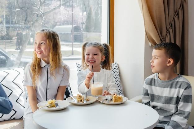 Uma grande e amigável companhia de crianças celebra o feriado em um café com uma deliciosa sobremesa. o dia do nascimento.