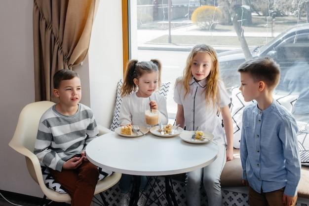 Uma grande e amigável companhia de crianças celebra o feriado em um café com uma deliciosa sobremesa.